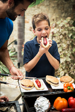 A boy and man at an open barbecue eating