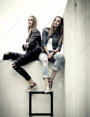 Two women on top of a concrete wall