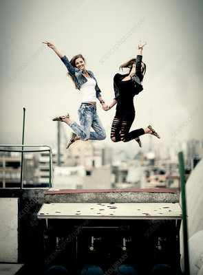 Two young women jumping on a rooftop