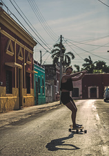 Woman riding a skateboard down a street