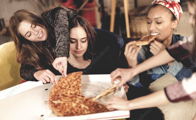 Four young women eating pizza