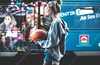 Young woman walking holding a basketball