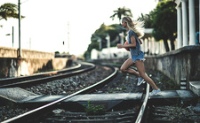 Young woman running across railway tracks