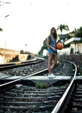 Woman on railway tracks with a basketball