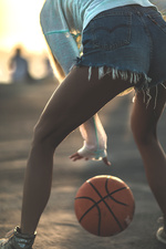 Woman standing bouncing a basketball
