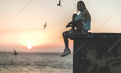 Young woman sitting on a wall at sunset