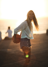 Young woman at sunset holding basketball