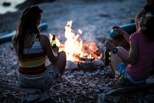 Young people on a beach around a campfire