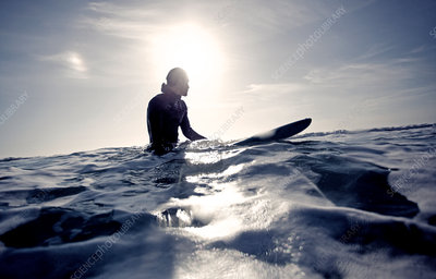Surfer in a wetsuit sitting on surfboard
