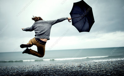 Man holding umbrella jumping on beach
