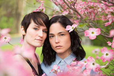Two women under branches of blossom