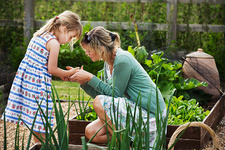 Woman and child, girl in vegetable patch