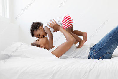 Woman on a bed holding up a young boy