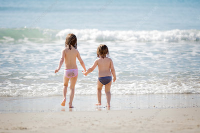 Two girls by the ocean, holding hands