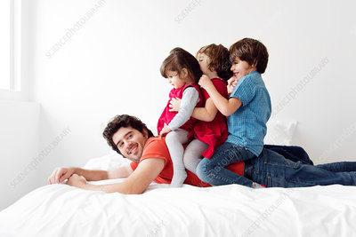 Man lying with three children on his back