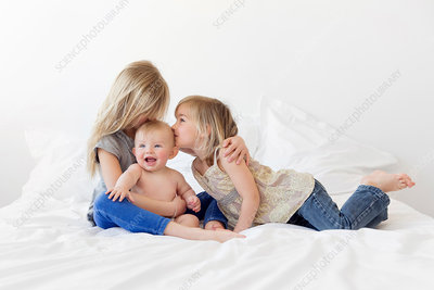 Two blond girls and a baby boy on a bed