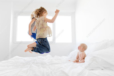 Baby on a bed with two girls jumping up