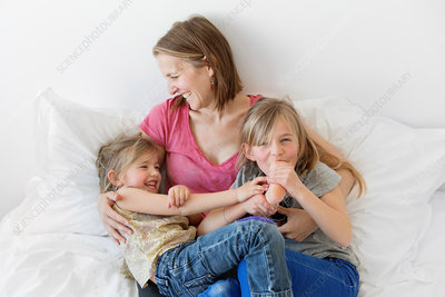 Woman sitting on a bed hugging two girls