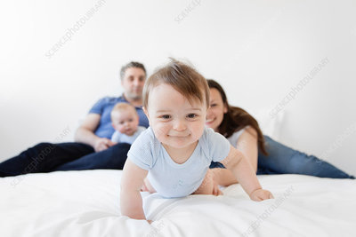 Family with a baby boy crawling on bed