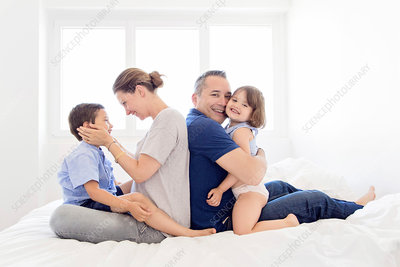 Family sitting on a bed, hugging