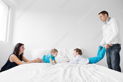 Man, woman , boy and baby boy on a bed