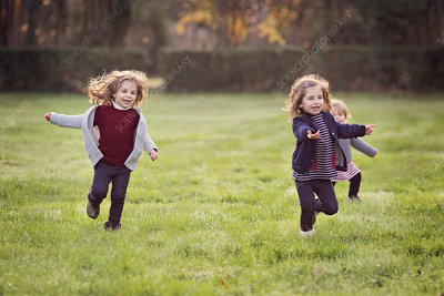Three young girls running across a lawn