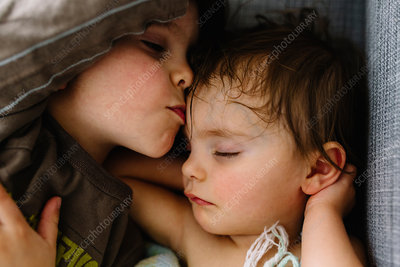 Boy kissing sleeping girl on forehead