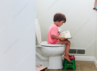 Boy sitting on the toilet reading a book