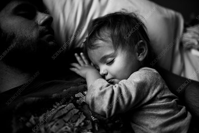 Father and baby girl cuddling, asleep