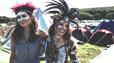 Two smiling girls in feather headdresses
