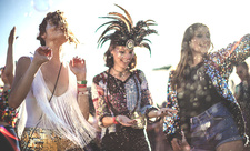 Women in feather headdresses dancing