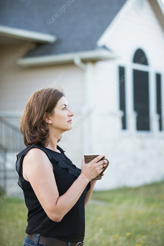 A woman outdoors holding a cup by a wall