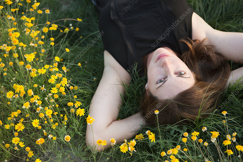 A woman lying on her back of grass