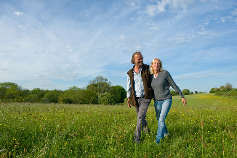 Man and woman walking across a meadow