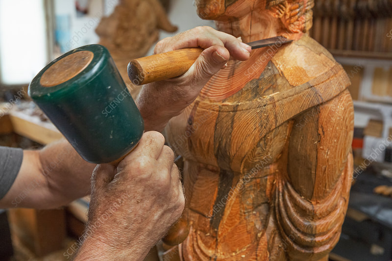 A wood carver with wooden figurehead