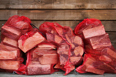 Stack of firewood in red net bags