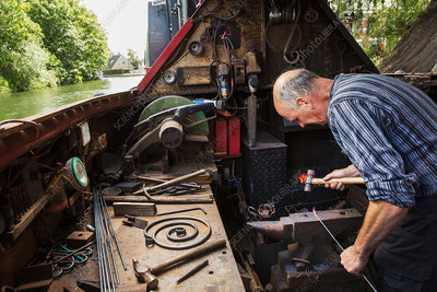 Blacksmith working at forge on narrowboat