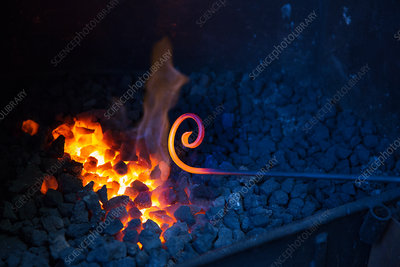 Metal rod in the hot coals of forge