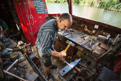 Blacksmith at his workbench on narrowboat
