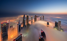 Skyscrapers above clouds in Dubai at dusk