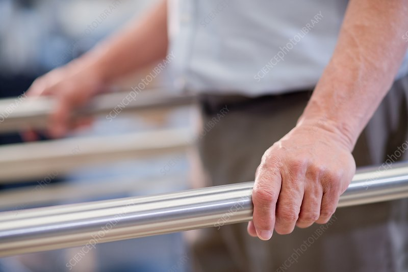 Man using parallel walking bars in hospital