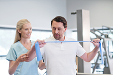 Nurse showing man how to use resistance band