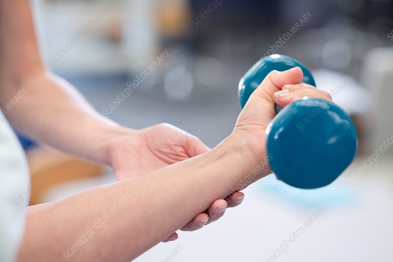 Person using hand weight with support of nurse