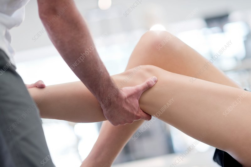 Physiotherapist massaging woman's leg