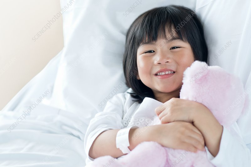 Girl in hospital bed with teddy bear