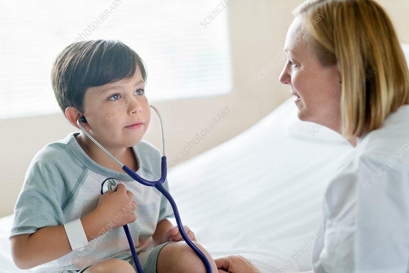 Boy wearing stethoscope with nurse
