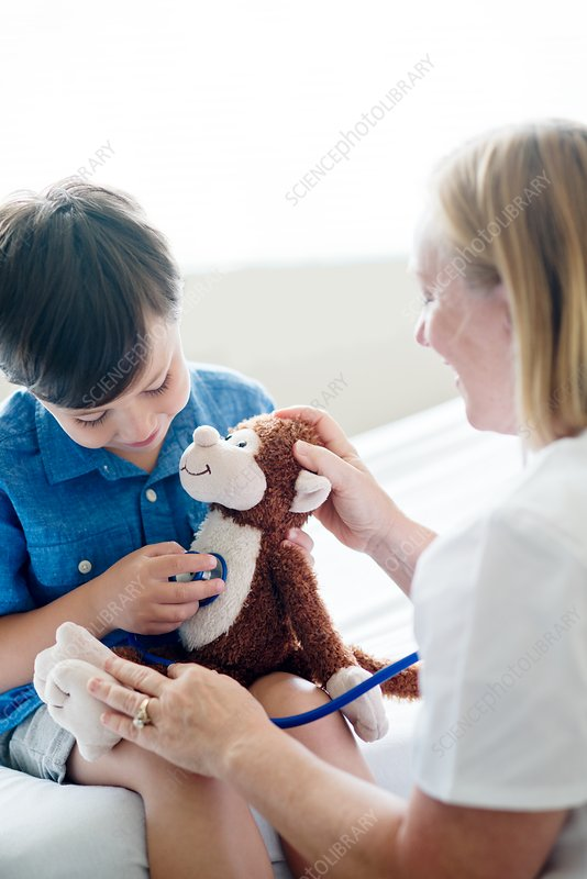 Boy playing with stethoscope and teddy bear