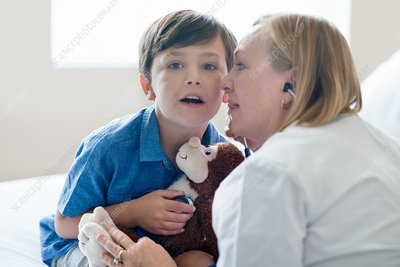 Boy and nurse listening to stethoscope