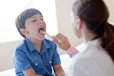 Boy with mouth open and tongue depressor