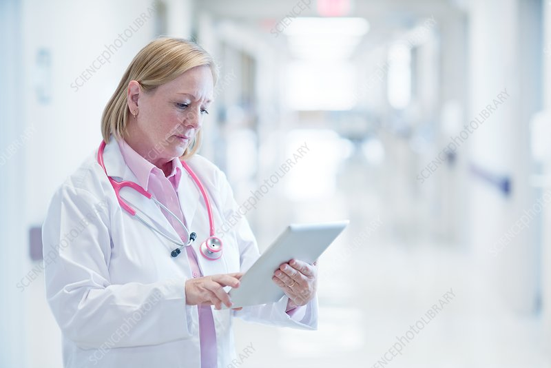 Mature nurse using digital tablet in hospital
